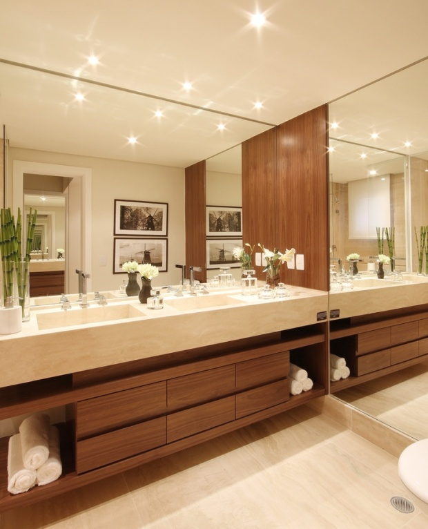 A cuba esculpida em mármore Travertino Romano é uma peça sofisticada e interessante. No banheiro do casal, ela deu destaque ao ambiente e ao gaveteiro em madeira