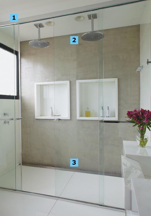 """1. Valioso principalmente em banheiros integrados ao quarto, o boxe vai até o teto e evita que o vapor se espalhe. Detalhe: é preciso haver janela ou exaustor dentro do compartimento. 2. Perfeitos para um casal, os chuveiros de teto (modelo 1997CTET, da Deca) simulam um banho de chuva. """"É o que se chama de água mole"""", explica Fábio. Repare nos dois orifícios embutidos no forro de gesso: são altofalantes do sistema de som (projeto da Home System). 3. A grelha substitui o ralo redondo com charme."""