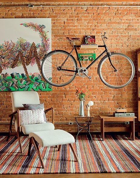 A bicicleta virou peça de decoração na sala. Ela está suspensa na parede de tijolinhos pela prateleira de madeira.