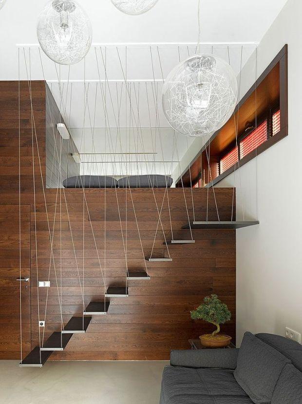 Escada em chapas de inox acoplada na parede sendo amarrada por fios de aço, imitando cordas.