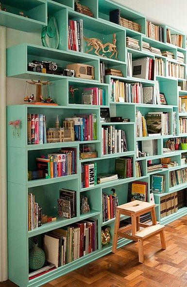 A estante de laca verde-água tem nichos de alturas e larguras diferentes, para acomodar vários tamanhos de livros